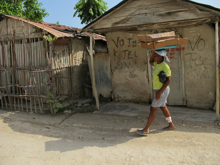 Wounded Haitian women walking down street holding boxes on her head